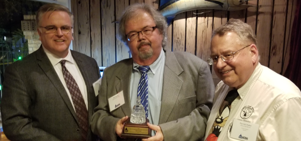 Industry Council for Tangible Assets chief operating officer David Crenshaw (left) and ICTA treasurer Patrick Heller (right), present Phil Darby (center) with the organization's Diane Piret Memorial Outstanding Service Award at the organization's dinner and update.